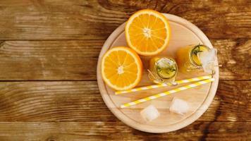 apelsinjuice på en träbricka. skivad apelsin och isbitar foto