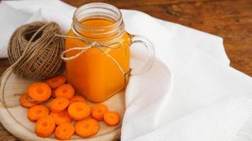 ljus apelsin morotsjuice och garngarn på träbakgrund foto