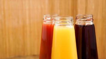 glasflaskor färsk frisk juice på träbakgrund foto