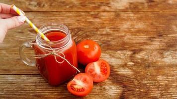 glas tomatjuice på träbord. färsk tomatjuice foto