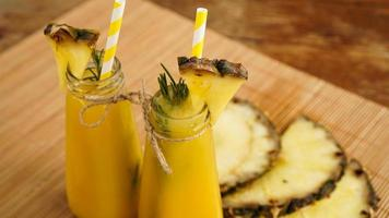 färsk ananasjuice med is i en liten glasflaska foto