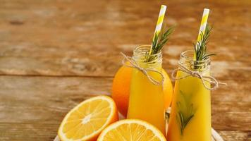 apelsinjuice i glasflaskor. saften är dekorerad foto