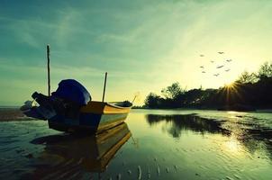 båt nära stranden när solen går ner foto