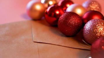 kuvert från hantverkspapper med julröda och rosa bollar på rosa foto