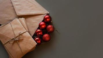 julkomposition. hantverkskuvert och röda bollar foto