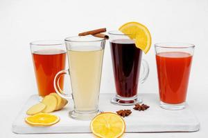 varmt te i glas koppar med citron ingefära på en vit bakgrund foto