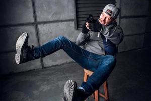 man med en kamera och ett roligt ansikte som sitter på en stol i en grå studio foto