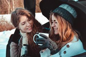glada vänner i vinterskogen. två tjejer sitter i bagaget och dricker kaffe foto
