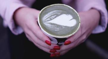 kvinnlig hand som håller varmt grönt te matcha latte i papperskopp. foto