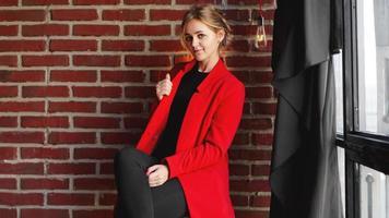 affärskvinna glatt leende bär röd jacka över kontors tegelvägg foto