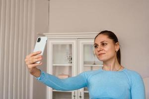 inomhusskott av vacker kvinna som bär sportkläder, tar selfie foto