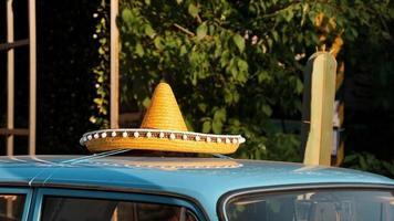 taket på en retrobil. mexikansk hatt på taket på bilen foto