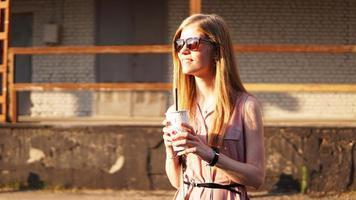 ung kvinna med en kopp limonad utanför foto