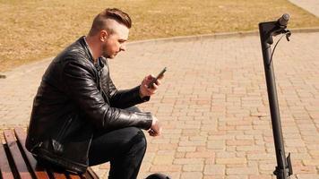 ung man sitter på en bänk en vårdag foto
