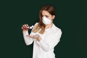 ung blond flicka i en vit blus och en mask foto