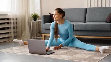 en vacker kvinna i en blå träningsdräkt sträcker sig foto
