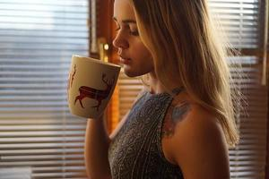 ung kvinna nära fönstret med en kopp te foto
