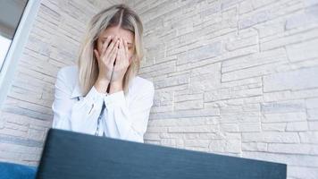 kvinna tittar på sin bärbara dator med ett smärtsamt oroligt uttryck foto