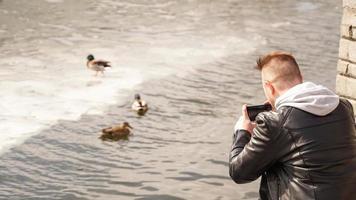 en ung man tar bilder av ankor på vattnet. vy bakifrån. foto