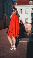 ganska ung kvinna i röd jacka på stadsgatan urban bakgrund foto