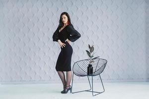 kvinna iklädd en svart klänning, röda örhängen poserar stående vid stolen foto