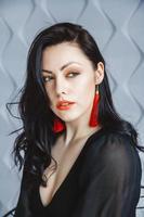 kvinna klädd i en svart klänning, röda örhängen i ljus studio foto