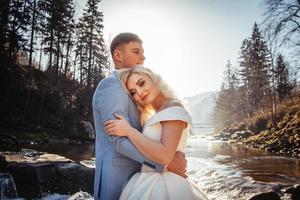 bröllopspar på berg och floder bakgrund i solnedgångarna foto