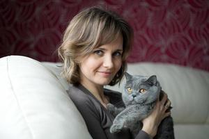 vacker ung kvinna som smeker en katt foto