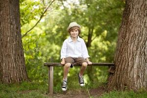 liten pojke i hatt, shorts foto