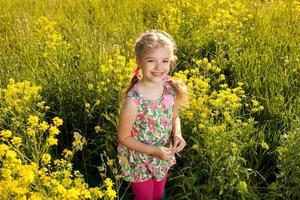rolig liten flicka bland gula vildblommor foto
