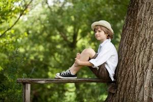 pojken sitter på en träbänk foto