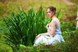 vacker kvinna i en blå klänning sitter på stranden av sjön foto