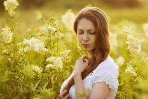 vacker ung kvinna med höga vildblommor foto