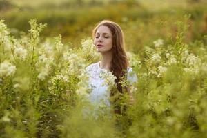 glad kvinna med stängda ögon bland vilda blommor foto