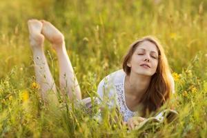 glad tjej med en bok i gräset som drömmer foto