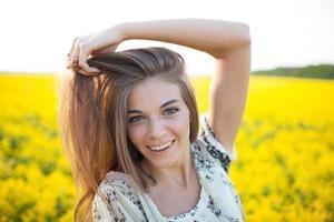 flicka med långt hår av gula vildblommor foto