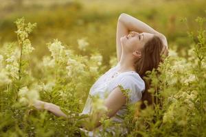 glad ung kvinna med höga vildblommor foto