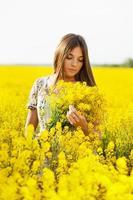 flicka som håller en bukett gula blommor foto