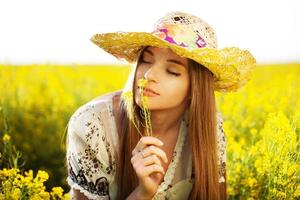glad tjej tycker om lukten av en blomma foto