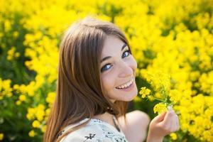 glad tjej med en gul blomma foto