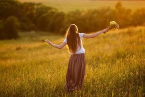 glad kvinna i fältet med en bukett blommor foto