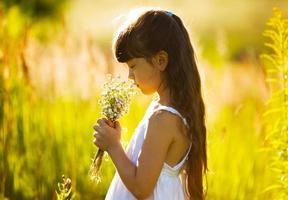 flicka med en bukett vildblommor foto