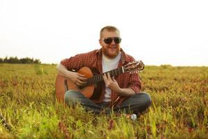 mannen i jeans sitter och spelar gitarr foto