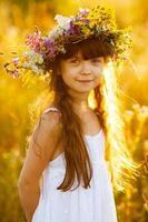 glad söt tjej som bär en krans av blommor foto