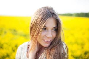 vacker flicka i ett fält av gula blommor foto