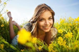 glad flicka ligger bland gula vildblommor foto