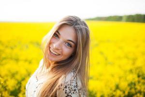 vacker ung kvinna av gula vildblommor foto