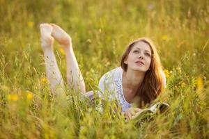 flicka med bok ligger i gräset och drömmer foto