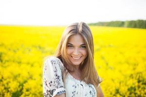 söt kvinna bland gula vildblommor på sommaren foto