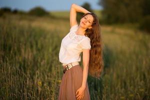 glad kvinna med långt hår på kvällen foto